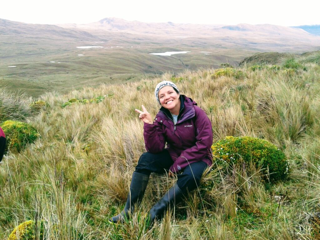 Photo: A smiling woman wearing a purple jacket and black wading boots flashes a 'peace' sign in the foreground of a mountainous landscape.