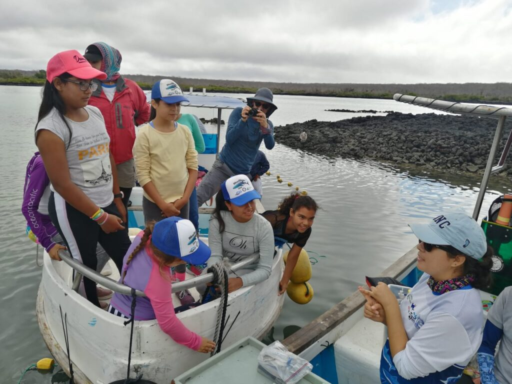 Photo: A woman wearing a 'UNC' cap speaks to a group of girls in a boat.