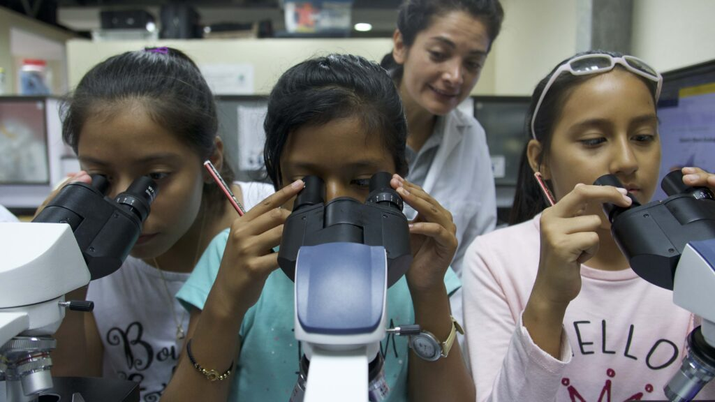 Photo: Three young girls look into microscopes. A smiling woman stands behind them in a white lab coat.