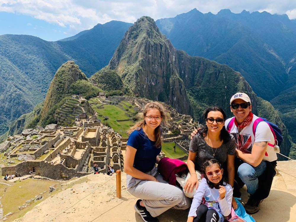 A man, a woman, and two girls pose above Machu Picchu.