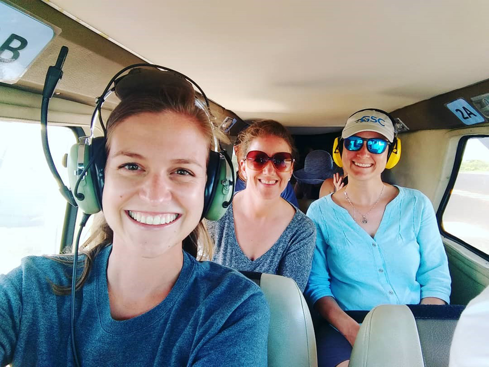 Photo: Three smiling women sit in the cockpit of a small plane.