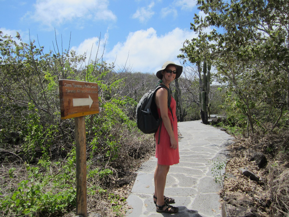 Photo: A woman wearing a pink skirt, backpack, and sun hat smiles in front of a trail marker.